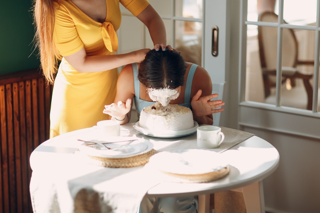 A person sitting at a table with a cake