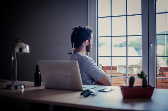 A person sitting at a desk in front of a window